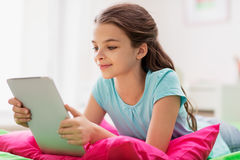 Smiling girl with tablet pc lying in bed at home Stock Photo