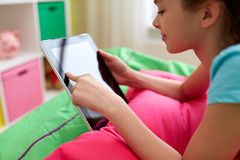 Smiling girl with tablet pc lying on bed at home Royalty Free Stock Photos