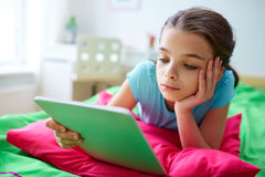 Smiling girl with tablet pc lying in bed at home Royalty Free Stock Images