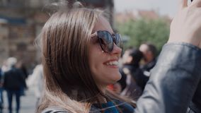 Smiling girl takes photo city`s of tourist attractions on cell phone stock video footage