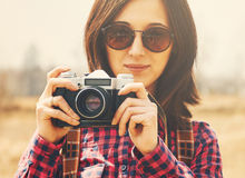 Smiling girl takes photographs with vintage photo camera Stock Image