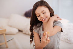Smiling girl taking care of her wound on the elbow Royalty Free Stock Photos
