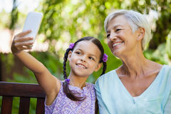 Smiling girl taking selfie with grandmother. At backyard Stock Image