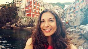 Smiling girl taking selfie photo in Riomaggiore, Cinque Terre, Italy. Vintage filter. Stock Image