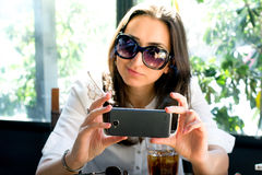 Smiling girl taking selfies with her phone, drinking and smoking Stock Photo