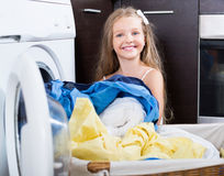 Smiling girl taking washed linen out Stock Photo