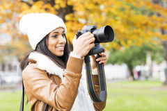 Smiling girl talking pictures outdoor. Royalty Free Stock Image