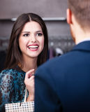 Smiling girl talks to shop assistant. Smiling girl with long dark hair talks to shop assistant Stock Photo