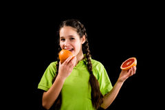 Smiling girl tasting sliced red grapefruit Royalty Free Stock Photography
