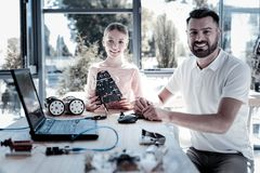 Smiling girl and teacher smiling while spending time in workshop. Transmitting knowledge. Friendly looking mature gentleman and his preteen student grinning Royalty Free Stock Photography