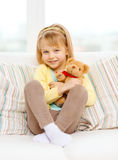 Smiling girl with teddy bear sitting on sofa Royalty Free Stock Photography