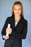 Smiling girl-teenager with book. Beautiful blue-eyed smiling girl-teenager in business suit with book, on blue background Royalty Free Stock Photo