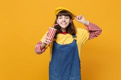 Smiling girl teenager in french beret, denim sundress holding plastic cup of cola or soda isolated on yellow wall. Background in studio. People sincere emotions royalty free stock image