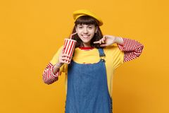 Smiling girl teenager in french beret, denim sundress holding plastic cup of cola or soda on yellow wall. Background in studio. People sincere emotions stock image