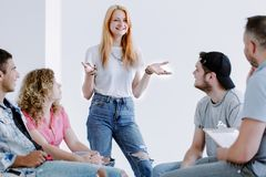 Smiling girl and teenagers. Smiling girl talking about her experiences of independent living during meeting with teenagers Royalty Free Stock Photos