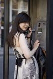Smiling girl in telephone booth calling Royalty Free Stock Image