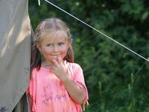 Smiling girl by a tent. Little girl that is smiling by a tent royalty free stock photo