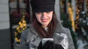 Smiling Girl Texts Outdoor. Smiling brunette in gray coat and black hat texting on the phone outdoor, christmas shot stock video