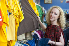 Smiling girl in thrift store 2. Smiling girl in thrift store looking at used t-shirts Royalty Free Stock Images