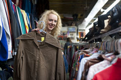 Smiling girl in thrift store. Holding very large collared vintage shirt Stock Photos