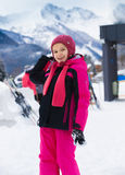 Smiling girl throwing snowball at highland resort Royalty Free Stock Photography