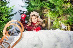 Smiling girl throwing snowball from the snow tower Stock Images