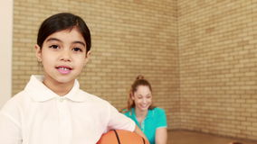 Smiling girl with thumbs up holding basketball. At the elementary school stock video