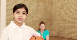Smiling girl with thumbs up holding basketball. At the elementary school stock video footage