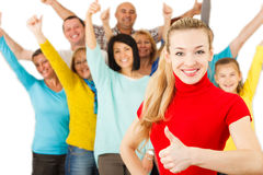 Smiling girl with thumbs up with large group of people on backgr Royalty Free Stock Photography