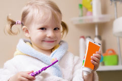 Smiling girl with toothbrush and tube Stock Image