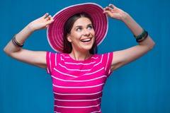 Smiling girl touching her beach hat. Stock Photo