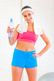 Smiling girl with towel holding bottle of water Royalty Free Stock Photos