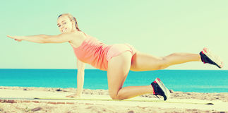 Smiling girl in track-suit  practice  yoga at sea beach Royalty Free Stock Photos