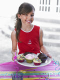 Smiling Girl With Tray Of Cupcakes Stock Photography