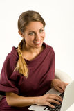Smiling girl in a trendy top using a laptop Royalty Free Stock Photography