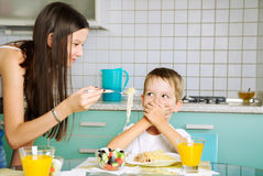Smiling girl trying to feed little boy. he closed mouth by the h Royalty Free Stock Images