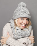 Smiling girl trying to stay warm wearing winter clothing Stock Image