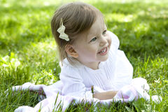 Smiling girl two years old lying on grass Royalty Free Stock Photo