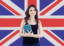 Smiling girl on the UK flag background. Pretty cheerful woman learning english language and traveling in United Kingdom.  royalty free stock image