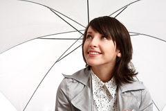 Smiling girl with an umbrella. Smiling girl with umbrella - girl looking up with hope the weather will change stock image