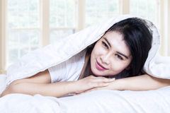 Smiling girl under blanket Royalty Free Stock Image