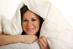 Smiling girl under white blanket Royalty Free Stock Image