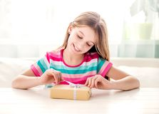 Smiling girl unwrapping present box. Smiling teen girl unwrapping gift box. Curious girl unpacking presents sitting at a table at home. Celebration holiday Royalty Free Stock Images