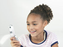 Smiling Girl Using Cellphone Stock Image