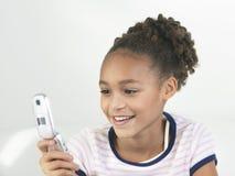 Smiling Girl Using Cellphone Stock Image