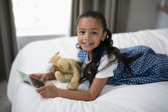 Smiling girl using digital tablet while lying on bed at home Royalty Free Stock Photos