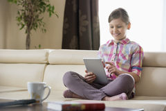 Smiling girl using digital tablet on sofa at home Royalty Free Stock Photography
