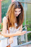 Smiling girl using her mobile phone Royalty Free Stock Image