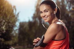 Smiling girl using her smartphone while training Stock Images
