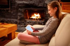 smiling girl using iPad digital computer tablet on bed for education or playing game royalty free stock images